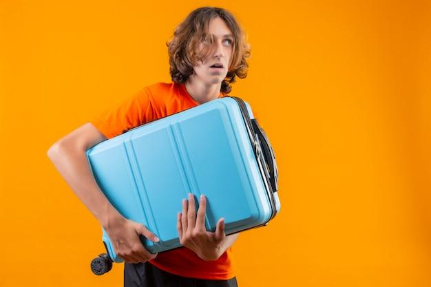 オレンジ色のtシャツを保持している若いハンサムな男旅行かばんが黄色のひざの上に立って困惑した表情でよそ見