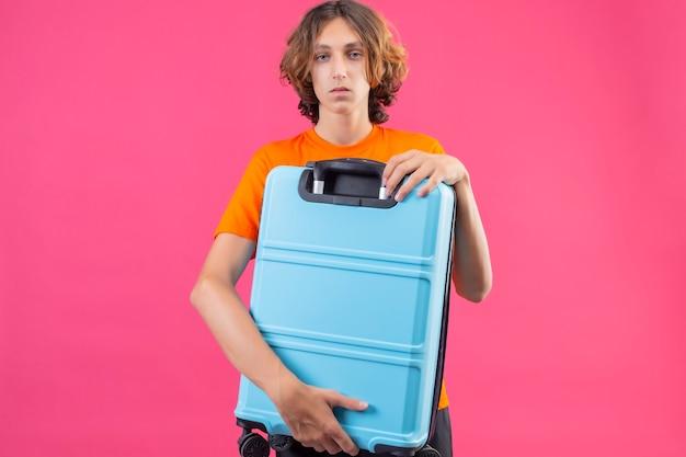 ピンクの背景の上に立って悲しい顔でカメラを見て旅行スーツケースを保持しているオレンジ色のtシャツの若いハンサムな男