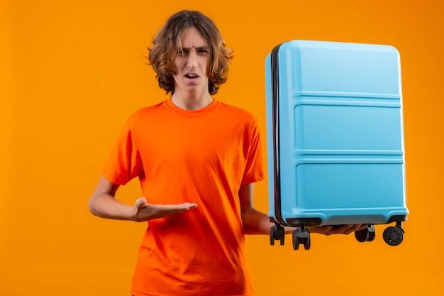 Молодой красивый парень в оранжевой футболке держит дорожный чемодан, указывая рукой, выглядит смущенным, стоя на желтом фоне