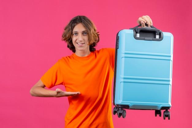 Молодой красивый парень в оранжевой футболке держит дорожный чемодан, указывая рукой, улыбаясь, со счастливым лицом, стоящим на розовом фоне