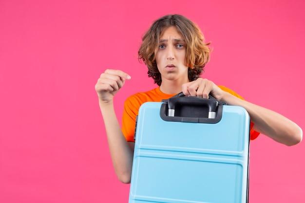 ピンクの背景の上に立っている不幸な顔とそれに指で指している旅行スーツケースを保持しているオレンジ色のtシャツの若いハンサムな男