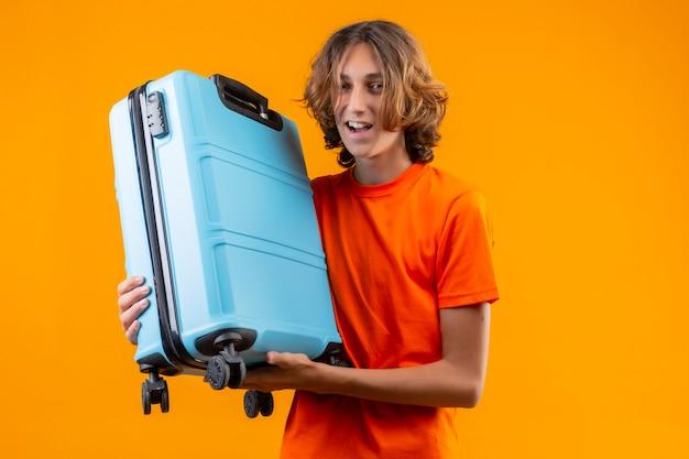 Молодой красивый парень в оранжевой футболке держит дорожный чемодан позитивным и счастливым, улыбаясь, весело стоя на желтом фоне