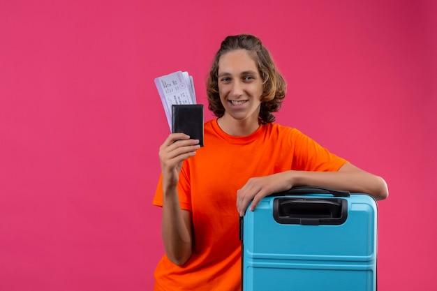 Молодой красивый парень в оранжевой футболке стоит с чемоданом и держит авиабилеты, глядя в камеру, улыбаясь счастливым и позитивным на розовом фоне