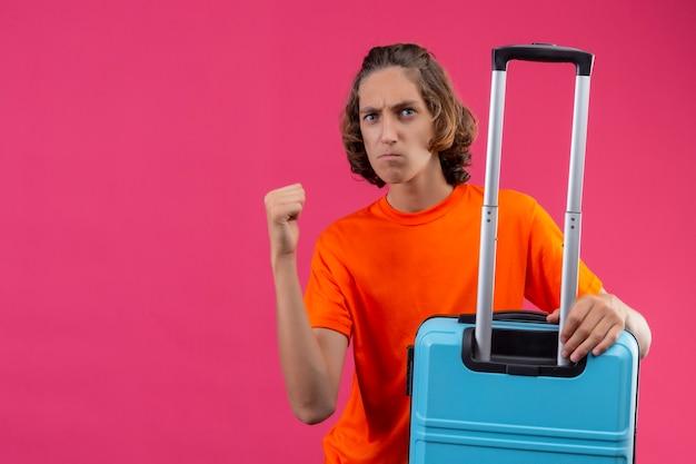 ピンクの背景に怒りの表現で拳を上げる旅行スーツケースで立っているオレンジ色のtシャツの若いハンサムな男