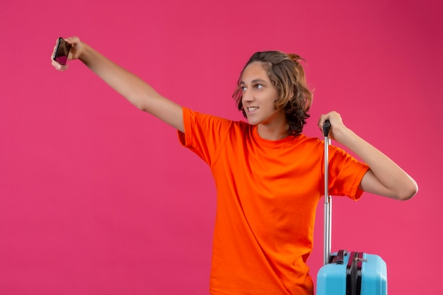 Молодой красивый парень в оранжевой футболке, стоящий с дорожным чемоданом, делает селфи с помощью смартфона счастливым и позитивным на розовом фоне