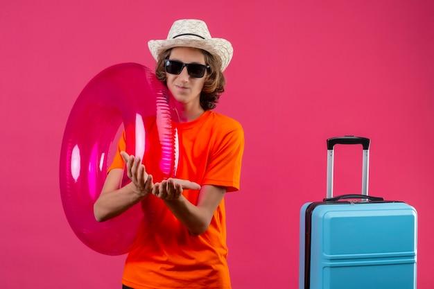 ピンクの背景の上のお金を求めて一緒に折り畳まれた手で旅行スーツケースを持って立っているインフレータブルリングを保持している黒いサングラスをかけているオレンジ色のtシャツの若いハンサムな男