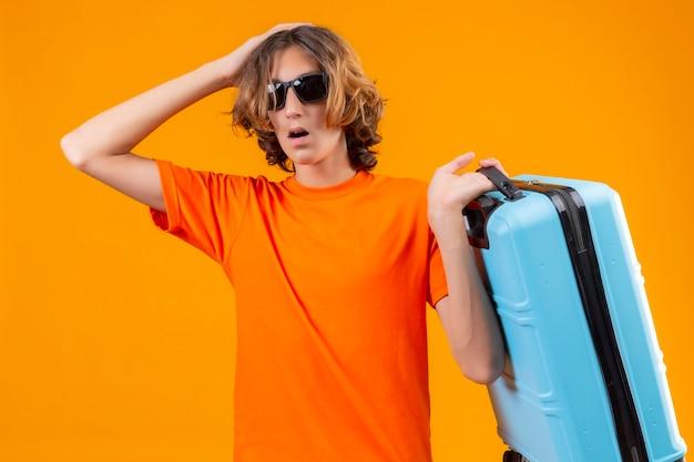 Молодой красивый парень в оранжевой футболке, одетый в черные солнцезащитные очки, держит дорожный чемодан, стоящий с рукой на голове за ошибку, выглядит смущенным, помнит ошибку на желтом фоне
