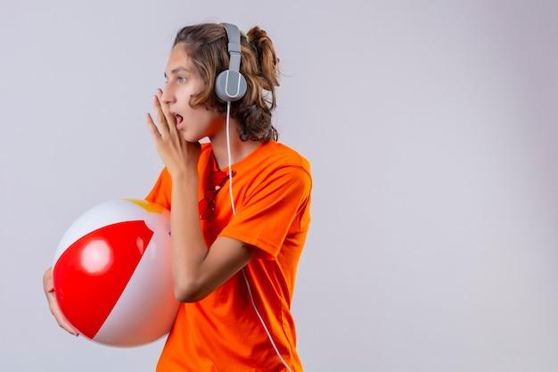 Молодой красивый парень в оранжевой футболке с наушниками держит надувной мяч, глядя в сторону, рассказывая секрет рукой возле рта, стоя на белом фоне
