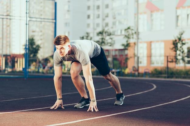 スタジアムで朝の若いハンサムな男。彼はスポーツウェアを着て、ヘッドフォンで音楽を聞いて、走りに行きます。