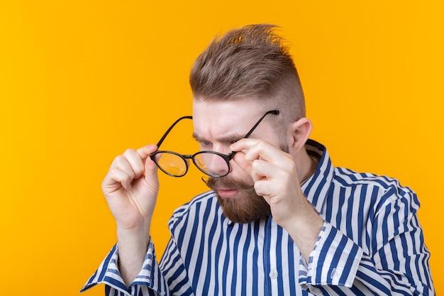 젊은 잘 생긴 남자가 서있는 동안 그의 안경을 찾고 있습니다.