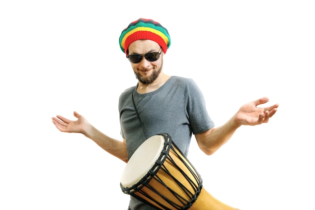 Young handsome guy learns to play the djembe drum instrument on a white background.