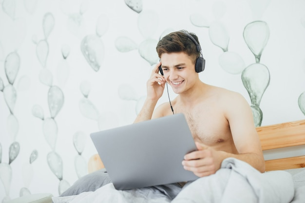 The young handsome guy listens to music on his laptop in the morning bed