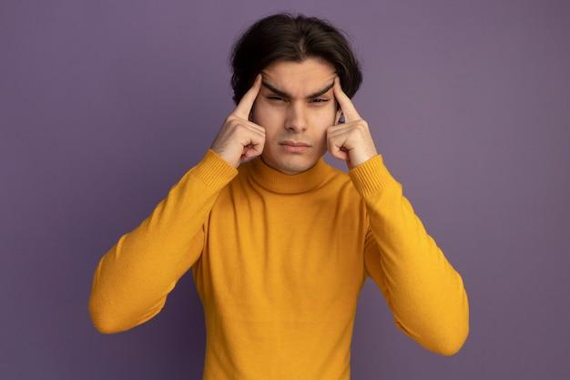 紫の壁にアジアのジェスチャーをしている黄色のタートルネックのセーターを着てカメラを見ている若いハンサムな男