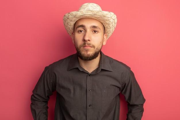 분홍색에 고립 된 검은 색 티셔츠와 모자를 쓰고 똑바로보고있는 젊은 잘 생긴 남자