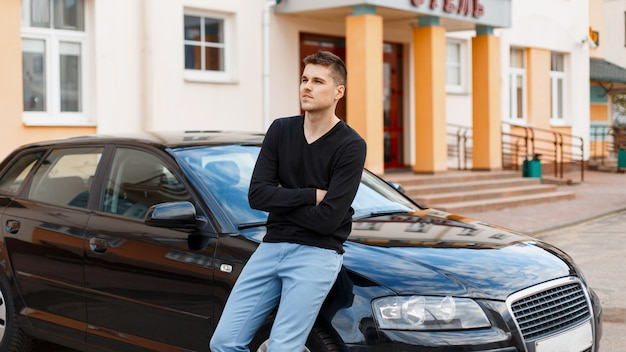 Young handsome guy near a black car