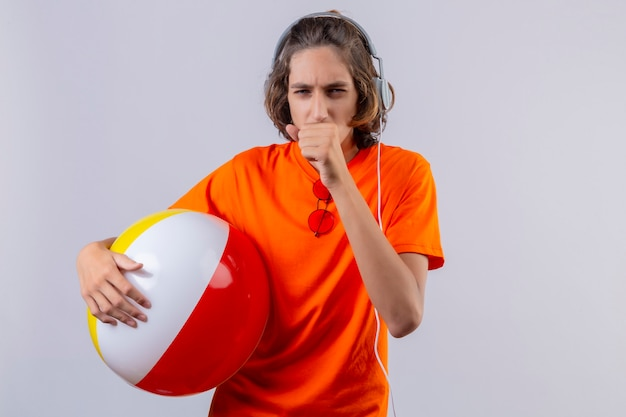 Young handsome guy in orange t-shirt holding inflatable ball with headphones coughing looking unwell standing