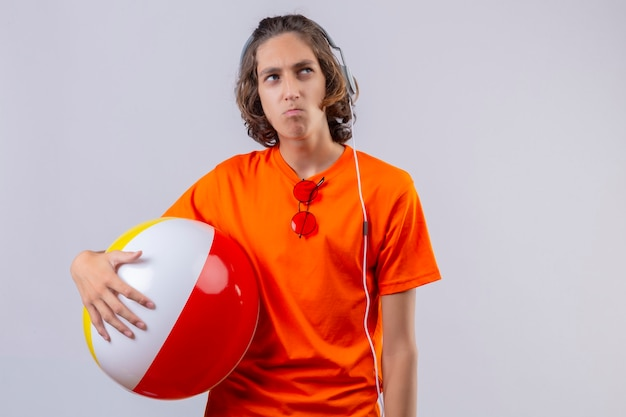 Young handsome guy in orange t-shirt holding inflatable ball with headphones displeased looking aside with frowning face standing over white background