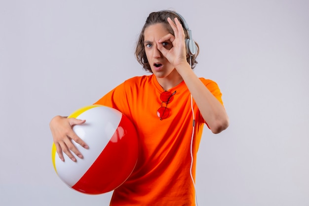 Young handsome guy in orange t-shirt holding inflatable ball with headphones doing ok sign looking through this sign surprised standing over white background