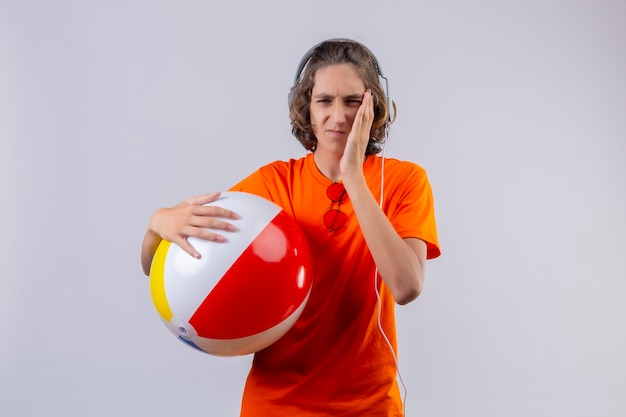 Young handsome guy in orange t-shirt holding inflatable ball with headphones looking unwell touching cheek having toothache standing over white background