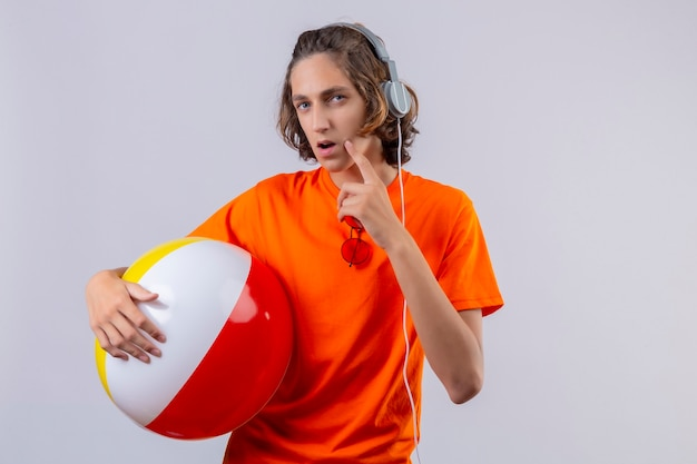 Young handsome guy in orange t-shirt holding inflatable ball with headphones standing with pensive look looking uncertain over white background
