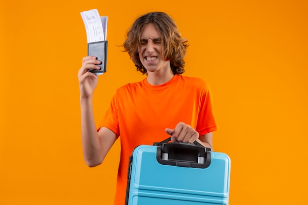 Young handsome guy in orange t-shirt holding travel suitcase and air tickets standing with closed eyes making desirable wish