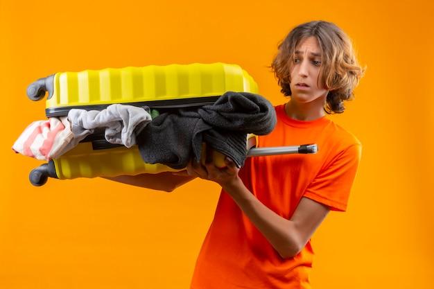 Giovane ragazzo bello in maglietta arancione che tiene la valigia di viaggio piena di vestiti che sembrano delusi con la faccia infelice in piedi su sfondo giallo