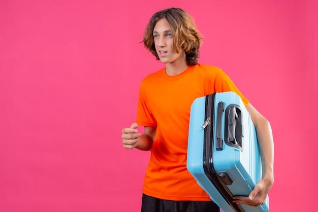 Giovane ragazzo bello in maglietta arancione che tiene la valigia di viaggio che osserva da parte sorridente in piedi su sfondo rosa