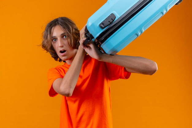 Young handsome guy in orange t-shirt holding travel suitcase looking at camera scared threatening to hint with suitcase standing