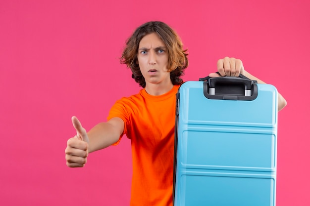 Giovane ragazzo bello in maglietta arancione che tiene la valigia di viaggio che guarda l'obbiettivo sorpreso che mostra i pollici in su in piedi sopra fondo rosa