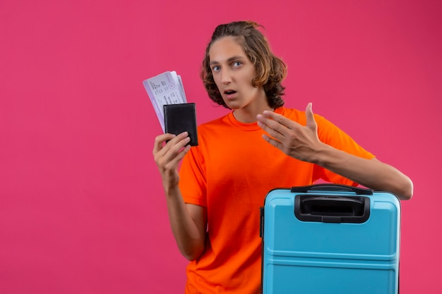 Young handsome guy in orange t-shirt standing with travel suitcase holding air tickets looking confused with arm raised over pink background
