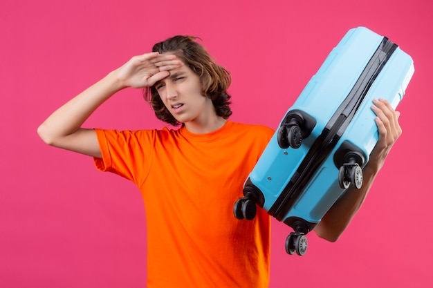Young handsome guy in orange t-shirt standing with travel suitcase looking tired and bored over pink background