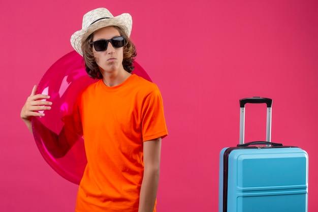 Giovane ragazzo bello in maglietta arancione e cappello estivo indossando occhiali da sole neri che tengono anello gonfiabile che osserva da parte con la faccia accigliata in piedi con la valigia da viaggio su sfondo rosa