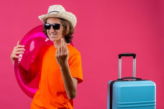 Giovane ragazzo bello in maglietta arancione e cappello estivo indossando occhiali da sole neri che tengono anello gonfiabile che mostra il dito medio positivo e felice in piedi con la valigia di viaggio su sfondo rosa