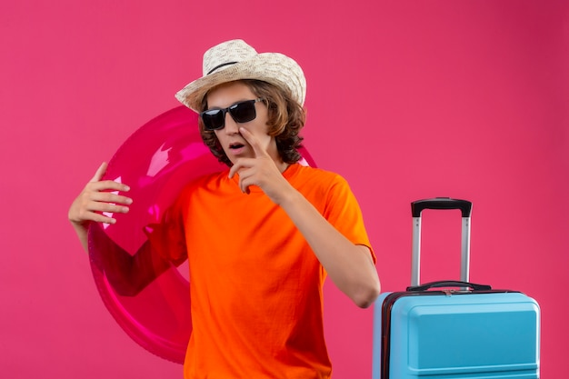 Young handsome guy in orange t-shirt and summer hat wearing black sunglasses looking at camera with pensive expressions thinking having doubts standing with travel suitcase over pink backgroun