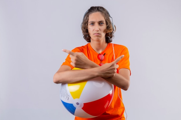 Young handsome guy in orange t-shirt with headphones holding inflatable ball crossing hands pointing with fingers to sides looking at camera with frowning face standing over white background