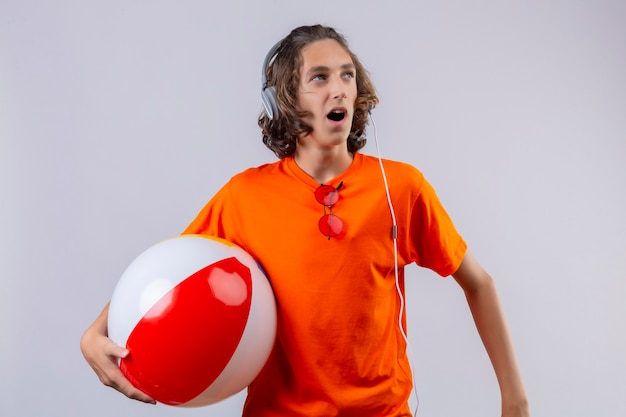 Young handsome guy in orange t-shirt with headphones holding inflatable ball looking aside surprised and amazed standing over white background