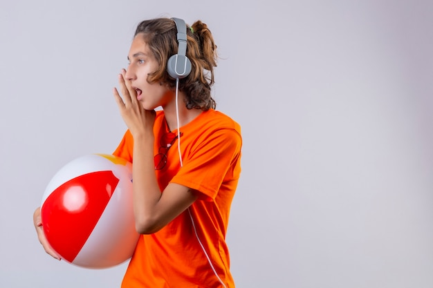 Young handsome guy in orange t-shirt with headphones holding inflatable ball looking aside telling a secret with hand near mouth standing over white background