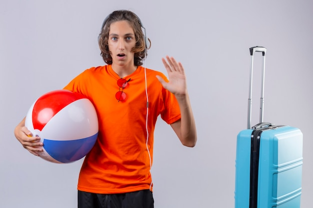 Young handsome guy in orange t-shirt with headphones holding inflatable ball looking surprised waving with hand standing near blue suitcase over white background