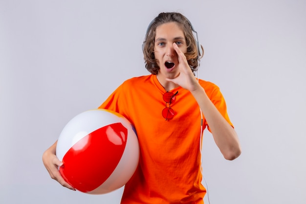 Young handsome guy in orange t-shirt with headphones holding inflatable ball shouting or calling someone with hand near mouth looking surprised standing over white background