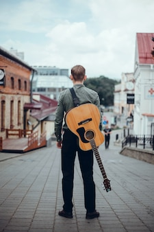 Young handsome guy plays the guitar, picks up a chord, street musician