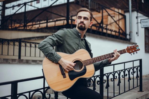 Молодой красивый парень играет на гитаре, берет аккорд, уличный музыкант
