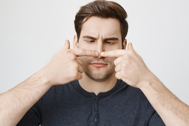 Giovane ragazzo bello che stringe il brufolo sul naso