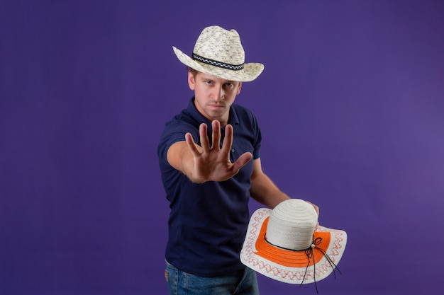 Young handsome guy in summer hat holding another hat standing with open hand making stop gesture with serious face over purple background