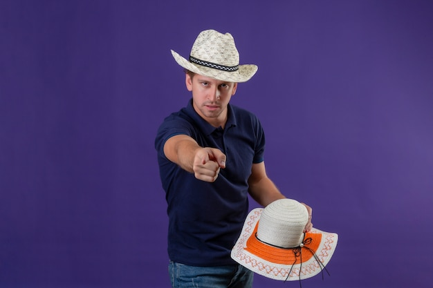 Young handsome guy in summer hat holding straw hat looking at camera with serious face pointing displeased and frustrated to the camera standing over purple background