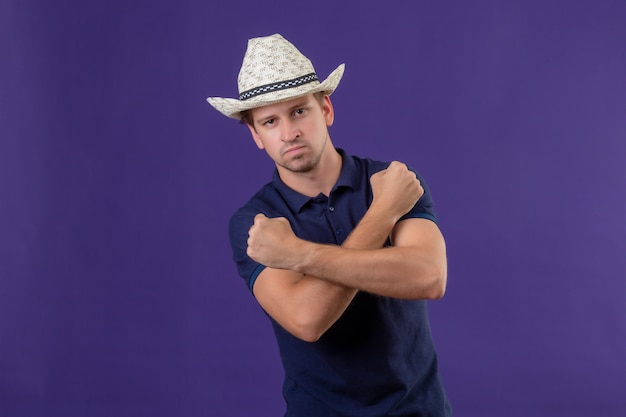 Young handsome guy in summer hat standing with arms crossed looking at camera with confident expression standing over purple background