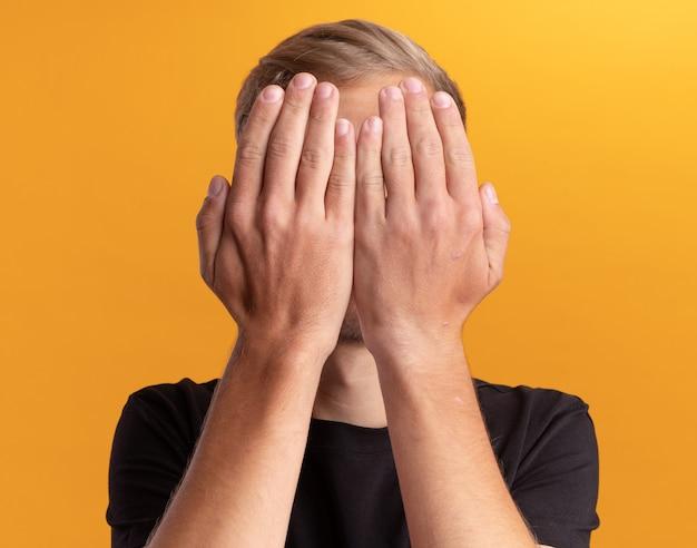 Giovane ragazzo bello che indossa la camicia nera ha coperto il viso con le mani isolate sul muro giallo