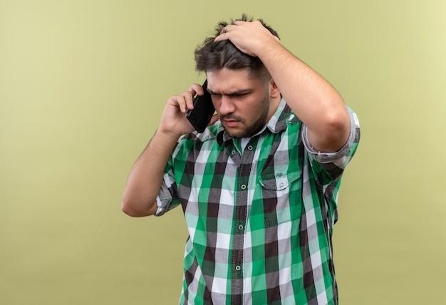 체크 무늬 셔츠를 입고 젊은 잘 생긴 남자가 카키색 벽 위에 서있는 전화 통화를 혼란스럽게합니다.