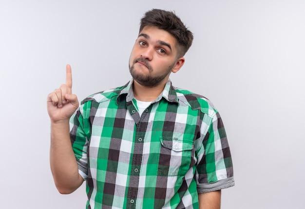 白い壁の上に立って人差し指をしている市松模様のシャツを着ている若いハンサムな男