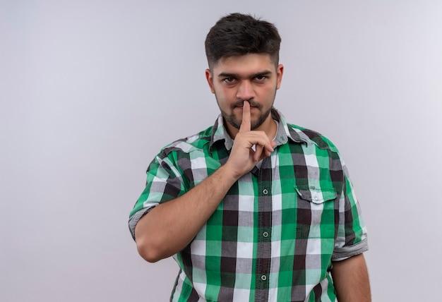 白い壁の上に立っている人差し指で沈黙のサインをしている市松模様のシャツを着ている若いハンサムな男