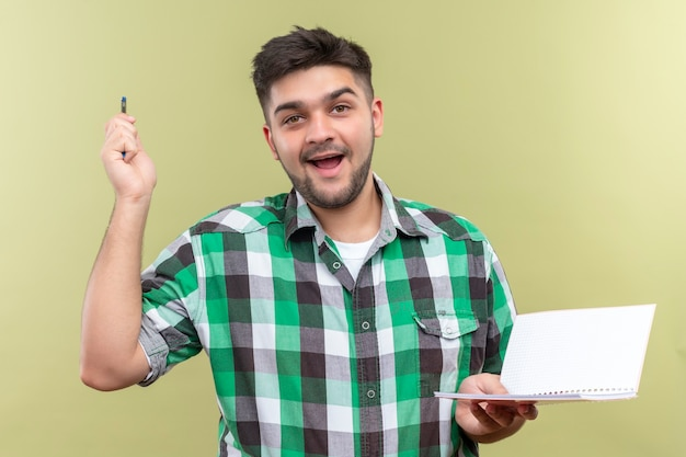 Young handsome guy wearing checkered shirt happily found the solution of problem holding pen and copybook standing over khaki wall